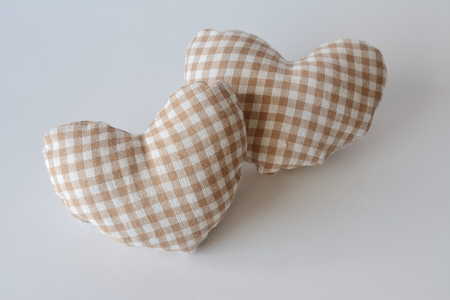 Two hearts with white cloth and white checkered beige, one over the other