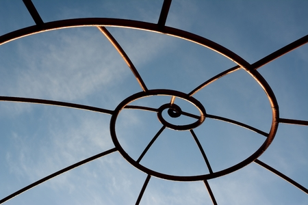 Metal frame with spiral forms under a blue sky Stock Photo