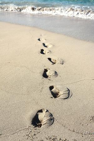 Footprints on the beach towards the sea Stock Photo