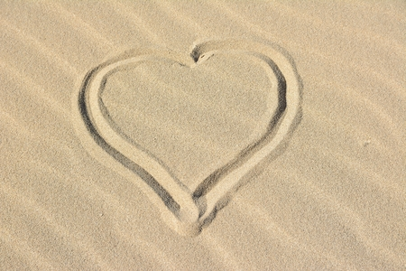 A heart painted with finger in the sand Stock Photo