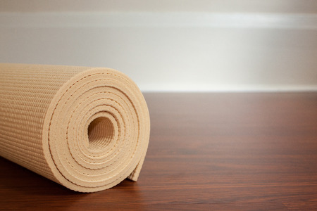 Light yellow yoga mat rolled up on brown wood floor with space for copy