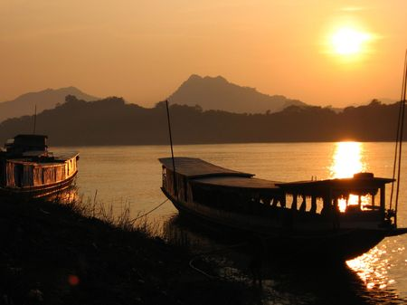asien: big boats on Mekhong bank at sunset