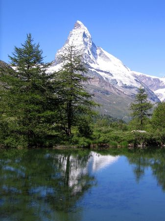 mount Matterhorn reflects from a wooded mountain lake
