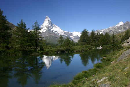 mount Matterhorn reflects in a wooded mountain lake Stock Photo