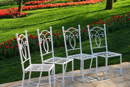 nicely: for white ornate chairs standing in a nicely tended park inviting to take a break