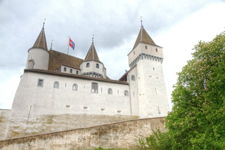 five towered white fairy tale castle Nyon standing on a lake geneva, Switzerland