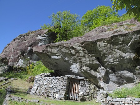 historic simple stable for cows, pigs or goats in Ticino formed by a rock ledge and a wall of piled stones photo