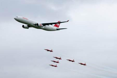 EMMEN - JULY 24: Swissair showcases it's latest plane an Airbus  A330-300 guarded by Tiger Jets of Patrouille Suisse at the Airshow 100 years Swiss aviation July 24, 2010 in Emmen, Switzerland.