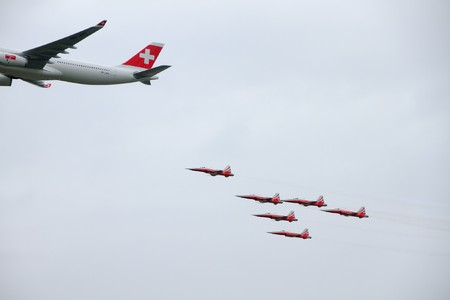 EMMEN - JULY 24: Swissair showcases it�s latest plane an Airbus  A330-300 guarded by Tiger Jets of Patrouille Suisse at the Airshow
