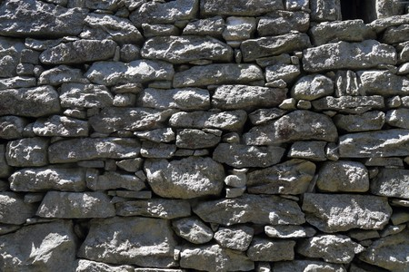 drystone: drystone wall put up put of grey rock slanted by the sun Stock Photo