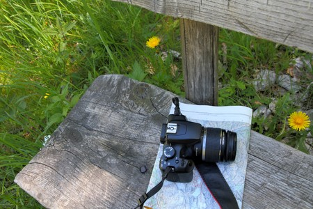 natures: map and camera on a wooden bend outside, concept for exploring nature, taking, nature pics, walking, hiking,being active,holidays,outings,enjoying the scenery,natures beauty, Stock Photo