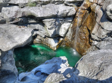 dropoff: green water of deep cut gorge of river maggia near Locarno Switzerland called Ponte Brolla