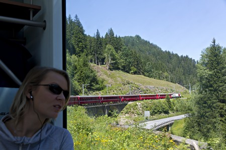 further: young pretty woman watches with amazement the alpine scenery pass by in the world famous swiss train Glacier Express, via earplugs she receives further information about train and scenery