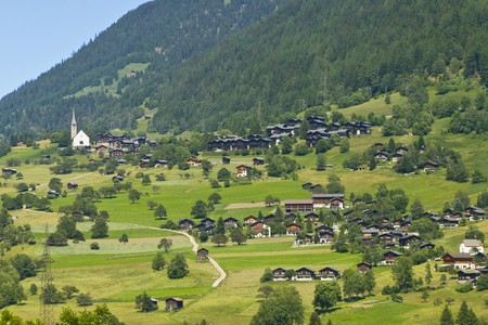 picturesque walser village with little church and traditional wooden houses with wide roofs in the swiss alps photo