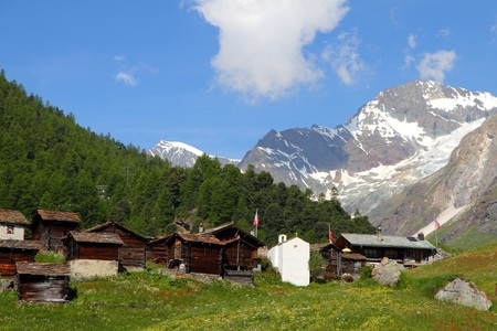 hugh: small swiss village settlement of wooden houses covered with stone roofes in front of forest and hugh snow covered alpine mountains on a sunny summer day in Wallis Switzerland