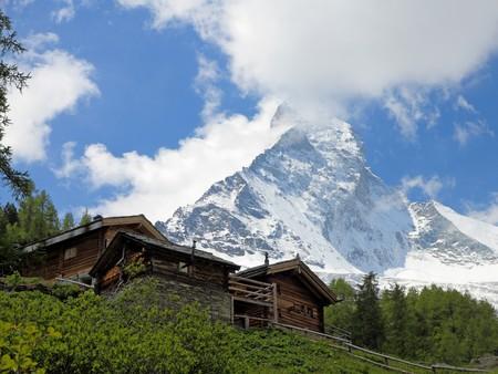 hugh: little wooden houses in front of the huge mountain Matterhorn near Zermatt in Switzerland