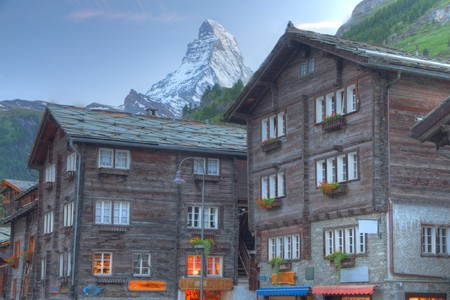 traditional swiss farmer houses built of dark wood in the centre of famous Zermatt with the mountain Matterhorn in the background at sunset photo