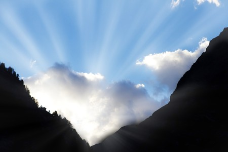 high end: sun bursts through clouds from a dark mountain valley symbol for hope,call not to give up,light at the end of the tunnel Stock Photo