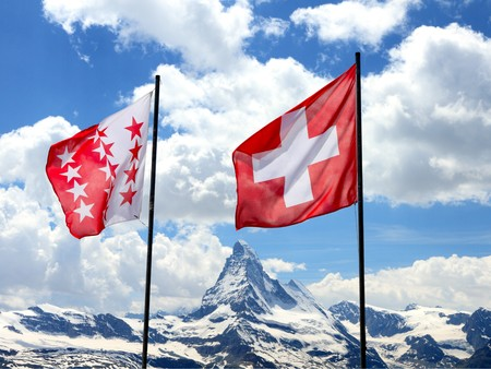 swiss flag and flag opf canton Valais fly in front of mountain Matterhorn range