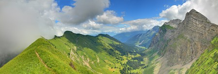 the swiss alps: panorama of a mountain valley formed by two steep ridges with settlement and lake on the bottom in summer seen from ridge, below mountain Bockmattli Stock Photo