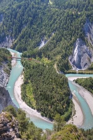 tight river bend filled with light blue water of Rhine Canyon in Switzerland seen from Flims and train Glacier Express crossing Rhine bridge photo