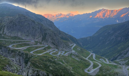 bridging: Old road with tight serpentines on the southern side of the St. Gotthard pass bridging swiss alps at sunset Stock Photo