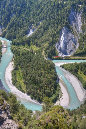 rail cross: tight river bend filled with light blue water of Rhine Canyon in Switzerland seen from Flims and train Glacier Express coming out of a tunnel Stock Photo