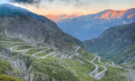 Antigua carretera con serpentines estrecha en el lado sur del paso de San Gotardo pasar el puente de los Alpes suizos al atardecer