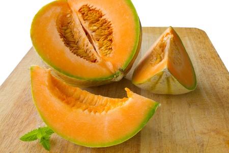 マスクメロン: ミントで飾られた木製の彫刻のボード上の新鮮なオレンジ メロンをスライス