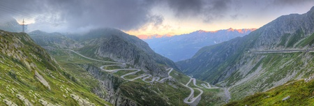 Panorama of old road with tight serpentines on the southern side of the St. Gotthard pass bridging swiss alps at sunset