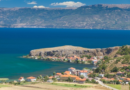 Mountainous rocky coatline of lake Ohrid in Macedonia dotted with red roofed houses in summer Stock Photo