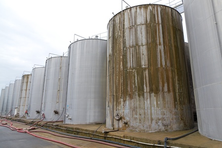 rows of large, old, oxidated, dirty, steel tank vessels  on a factory yard for storing liquids industrial style photo