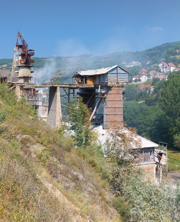 strange looking heavy, dusty,smoky industry on a steep mountain slope in Kosovo, Europe photo