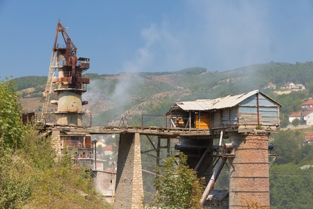 strange looking heavy, dusty,smoky industry on a steep mountain slope in Kosovo, Europe photo