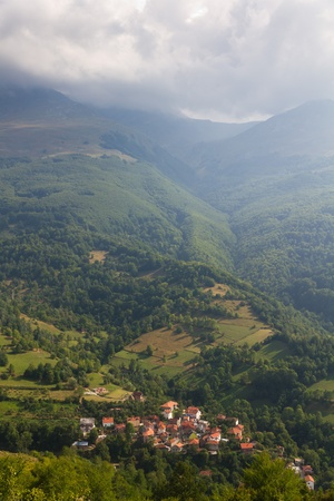 mountain village with red roofed houses in the wooded mountains with fog and clouds in Kosovo photo