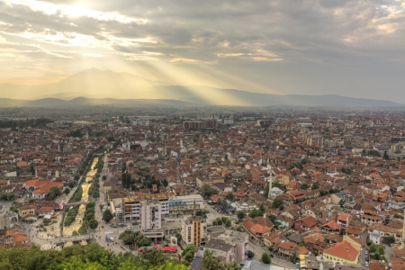 river scape: city scape of second bigest city Prizren in Kosovo at sunset with red roofed houses and mosques and river. In the background a mountain range. Stock Photo
