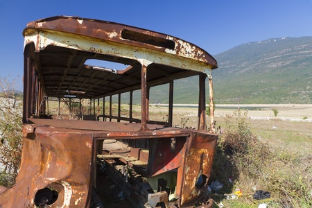 salvage yards: stripped rusty, old abandoned bus wreck in arid mountainous landscape of Montenegro