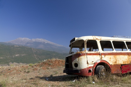 arid: stripped rusty, old abandoned red bus wreck in arid mountainous landscape of Montenegro