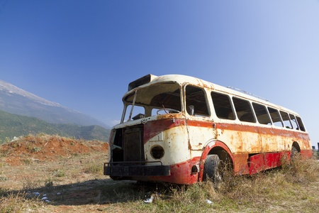 rust red: despojado de naufragio oxidado, antiguo el autob�s rojo abandonados en el �rido paisaje monta�oso de Montenegro
