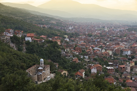 roofed house: city scape of second biggest city Prizren in Kosovo at sunset with red roofed houses, mosques and during war destroyed Serbian-Orthodox Savior Church. In the background a mountain range. Stock Photo