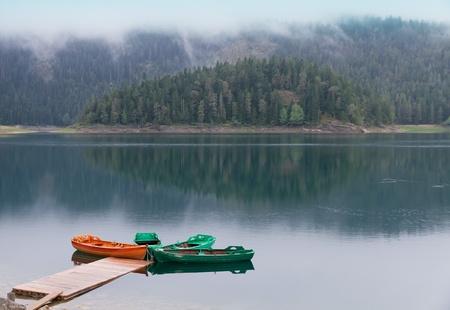 lagos: Tranquilo lago regado negro con barco pier, bosque reflejando en el patrimonio mundial de la UNESCO, Parque nacional Durmitor con niebla y nubes, Montenegro