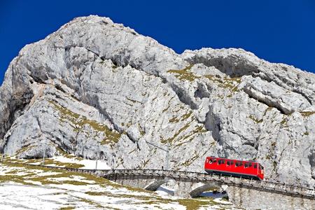 red cogwheel train serving tourists going up mountain Pilatus, Switzerland