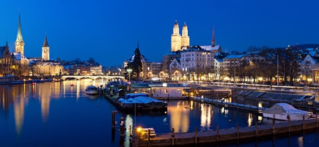 Panorama: Zurich, swiss fanancial center seen from river Limmat at night with historic city center and its churches reflecting in the stream