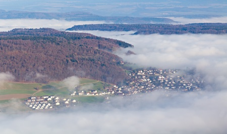 obscured: Villages half obscured by fog in hilly wooden landscape, Autumn, aerial view, Switzerland Stock Photo