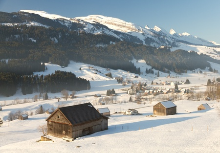 rural wooden cabins in valley with mountain tops of Churfirsten Switzerland,  photo