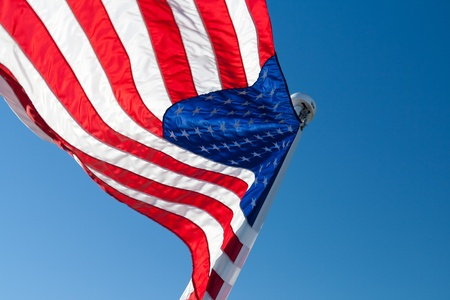 backlight: flying American backlight flag with copyspace against a blue sky