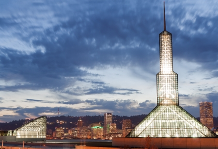 sunset in Portland with lighted distinct glass tower of Portland Convention center , Downtown in background