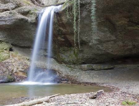 waterfall coming down over hollow cliff in the woods long exposure photo