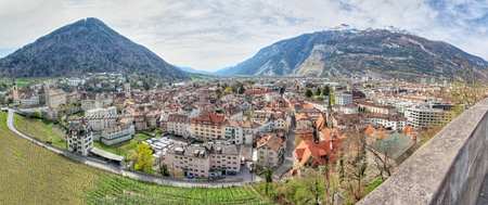 surrounded: Panorama of historic city center with church, castle  and old houses surrounded by vinyards and mountains in Chur, Switzerland