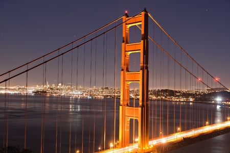 Illuminated Pylon of the Golden Gate bridge San Francisco at dusk in the surrounding bay photo